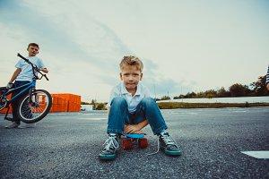 Boy sitting on penny board close-up