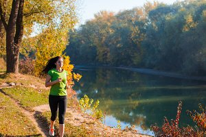 Young active woman jogging along the