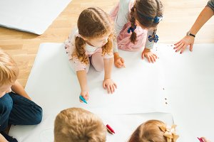 Top view of group of kids drawing on