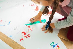 Girl painting with her fingers on a