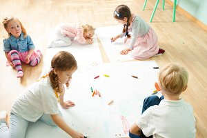 Top view of cute kids drawing on a