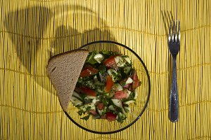 Salad and bread on a yellow bamboo m