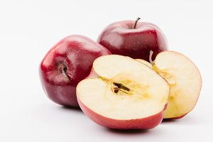 halved and whole tasty red apples on