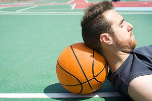 man lying on the basketball field