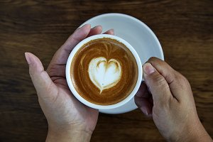 Hands holding coffee cup heart cup