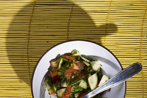 Salad on a yellow bamboo mat.