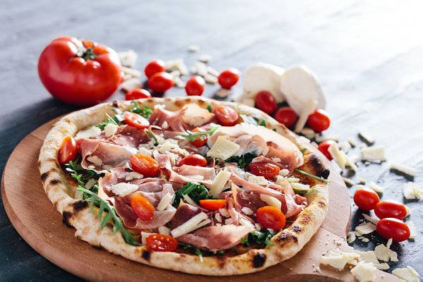 Pizza with ham, cheese, tomatoes an…