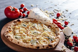 Four cheese pizza on wooden board.