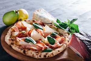 Pizza with ham, pear, basil and blue