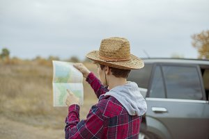 young man in hat with road map and b