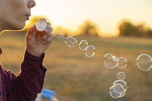 person blow soap bubbles on a sunset