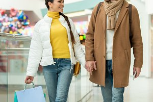 loving couple with shopping bags hol