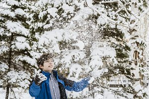 young teenager boy throw snow up in