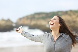 Excited woman holding smart phone