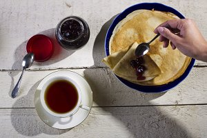 Pancakes with jam on a wooden backgr