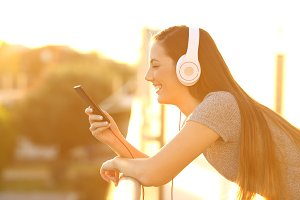 Girl listening to music at sunset