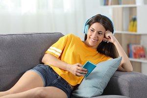 Happy teen in yellow listening