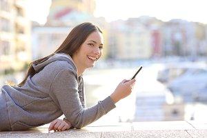 Happy teen holding phone looking