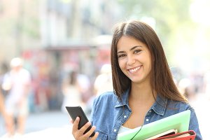 Happy student posing holding a phone