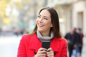 Happy woman holding phone looking