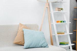 modern pillows on sofa near wooden l