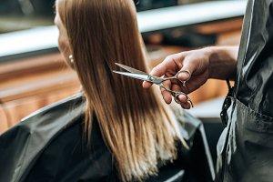cropped shot of hairdresser holding