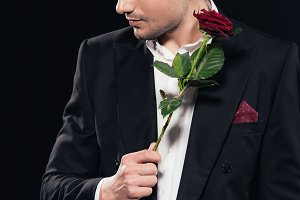man in suit holding red rose and loo