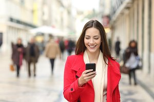 Happy woman walking using a cellphon