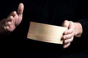 hands hold a round wooden sieve