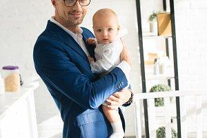 handsome businessman holding infant