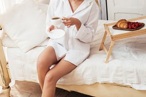 smiling woman holding coffee cup whi