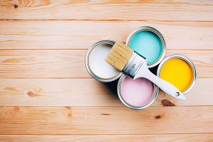 Four open cans of paint with brush