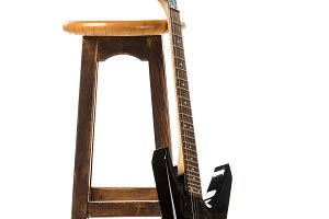 black electric guitar near wooden ch