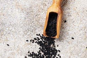 Black sesame seeds in wooden scoop