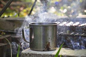 Iron mug with hot drink near fire