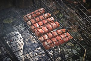 Grilling sausages wrapped becon on