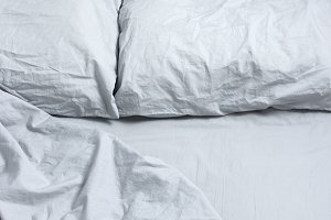 Messy bed with gray bedclothes