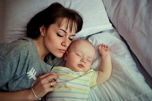 Baby sleeping in bed with mother