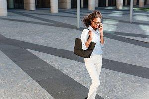 Modern businesswoman talking outside