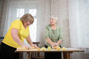 Two old women making little apple