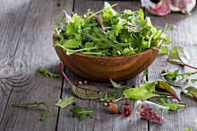 Green salad leaves in a wooden bowl