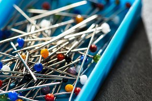 Many multicolored sewing pins in box