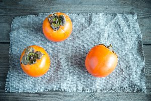 Fresh persimmons on the wooden table