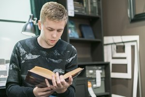 young man reading a science book in