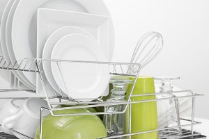 Green and white dishes on dish rack
