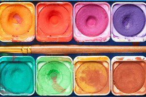 Watercolor paints and paintbrush