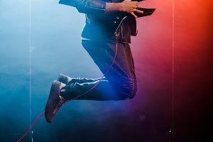 happy male musician jumping and perf