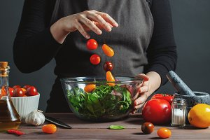 Chef pours cherry tomatoes in a bowl