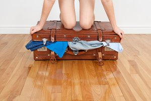 Woman closing overfilled suitcase