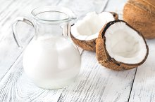 Jug of coconut milk with fresh cocon